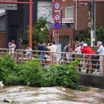 雨が上がり、川の様子を見る人々